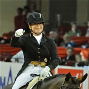 Isabell Werth reitet bereits mit Helm in der Prüfung.